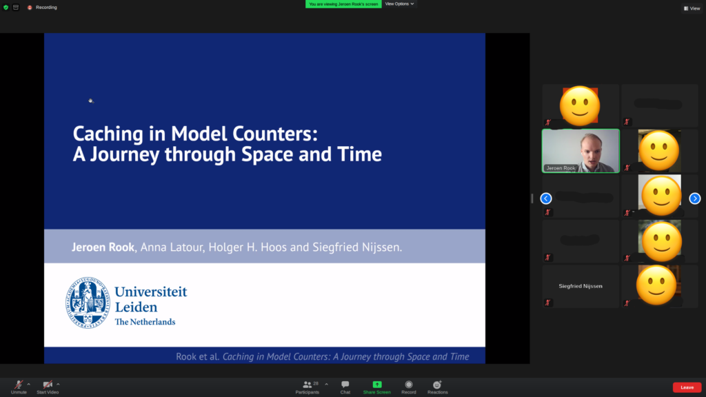 """Zoom screenshot of Jeroen's title slide, which reads: """"Caching in Model Counters: A Journey through Space and Time"""", by Jeroen Rook, Anna Latour, Holger Hoos and Siegfried Nijssen."""